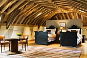 Twin sleigh beds with black, wooden frames in open-plan attic room with exposed wooden roof structure