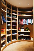 Children's clothing in semi-circular, wooden fitted wardrobe in dressing room