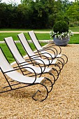 Elegant deckchairs with black metal frames and canvas seats on gravel in garden