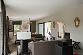 Torso on plinth in front of lounge area with sofa set in classic, modern interior