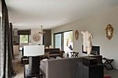 Torso auf Stele vor Loungebereich mit brauner Sofagarnitur in klassisch modernem Wohnraum