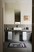 View through open door into simple bathroom with minimalist washstand counter against wall painted light grey to half height