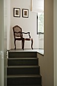 View through open door of antique, cane backed chair on staircase landing