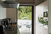 Designer kitchen with appliances in fitted cupboards and view of white, plastic Bauhaus chairs through open terrace door