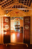 View through open doors in carved, wooden partition in traditional house