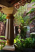 Colonial-style porch supported on massive column in tropical garden
