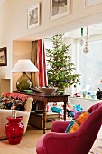 Decorated Christmas tree and wrapped presents in bay window; deep pink armchair and small, red, glass table shaped like demijohn in foreground