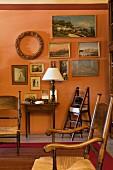 Antike Binsen-Armstühle vor apricotfarbener Wand mit einer Sammlung kleiner Landschaftbilder und antikem Wandtisch