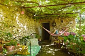 A young boy reads in a hammock in a shady vine-covered pergola with iron daybed