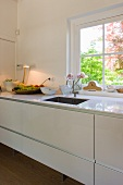 Modern kitchen counter with white base units in front of a window