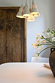Retro style hanging lamp with porcelain shades above a dining table in front of a rustic cupboard against a wall