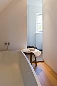 Wooden stool next to a modern bathtub in a minimalist bathroom