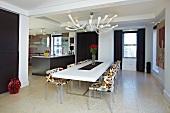 Offener Wohn-und Essraum im Designer-Retrostil mit modernem schwarz-weißem Interieur und gemusterten Stühlen an langer Tafel
