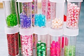 Assorted decorative beads and sequins in plastic tubes