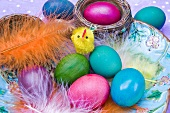 Easter eggs and feathers in a ceramic bowl