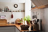 Open shelving and solid oak work surfaces in kitchen with white wooden wall panels
