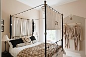 Iron four-poster bed adorned with vintage linen by Starched and Crumpled