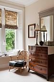 Antike Schubladenkommode neben niedrigem Windsorstuhl mit weichem Sitzpolster