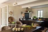 Cane chairs around a coated metal dining table in a kitchen with traditional beamed ceiling, Lacanche cooker and wire bowls