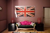Framed union jack flag above a sofa upholstered in a range of fabrics in bedroom with black chinese lacquer boxes and rugs