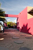 Inner courtyard of Hotelito with round paving stones and pink walls