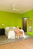 Queen bed in brightly painted green bedroom with wicker armchair and wicker framed mirror