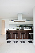 Bar stools in front of kitchen counter in an open kitchen