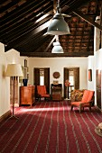 Indian residential house - designer standard lamp on striped carpet of living room with traditional furnishings and view of exposed roof structure