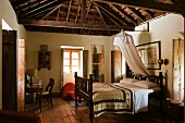 Double bed in traditional bed room of Indian residential house with exposed, wooden roof structure