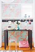 Black, metal console table and transparent, plastic stool against floral wallpaper