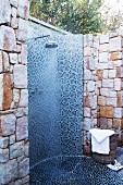 Outdoor shower with blue, mosaic tiles built into a natural stone wall