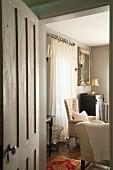 Einblick durch geöffnete Tür in Wohnzimmer im Vintagestil mit gemütlichen Sesseln und Wandkerzenhaltern