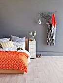 Double bed with modern, colourful bed linen next to dress hanging on clothes rack on grey wall