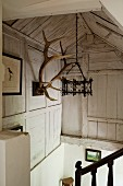 Stairwell with wrought iron pendant lamp hanging from exposed, wood-clad roof structure and antlers on wooden wall