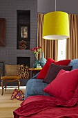 Comfortable couch with red scatter cushions and cosy, red blanket below bright yellow pendant lamp