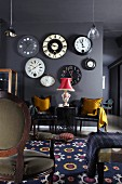 Collection of antique wall clocks on grey wall above elegant leather chairs with golden cushions