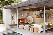 Seating area on roofed terrace next to pool with open fireplace, hanging chair & stools made from natural materials
