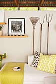 Chaise sofa with scatter cushions below pictures & old gardening tools decorating wall
