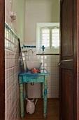 Badezimmer mit Waschtisch im Shabby Stil, angelehntem Badezimmerspiegel und einer modernen Waschschüssel aus Porzellan