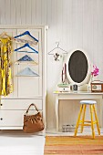 Dress and coathangers hanging on front of white-painted farmhouse wardrobe next to dressing table and yellow stool against white, wood-panelled wall