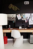 Classic shell chair in front of computer on wooden table against black wall with pinboard