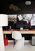 Klassiker Schalenstuhl an Holztisch mit Rechner vor schwarzer Wand und Pintafel