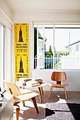 Klassikerstühle und Beistelltisch (Charles Eames)in heller Zimmerecke vor offenem Fenster