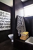 Modern bathroom with black mosaic tiles and striped towels hanging on toilet screen wall