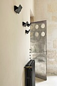 Beige wall with radiator, sconce lamps and steel door with circular cut-outs