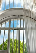 Large, double-height window with arched frame above terrace door and white, gauzy curtain