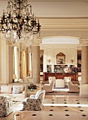 Hotel lobby with classic armchairs on glossy marble floor; Ionic columns and elegant bar in background