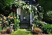 Offener Pavillon mit Kletterrosen berankt in blühendem Garten