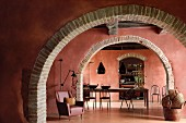 Brick red living room and dining room separated by arched doorways