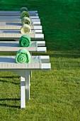 Massagebänke mit Handtuchrollen auf Rasenfläche